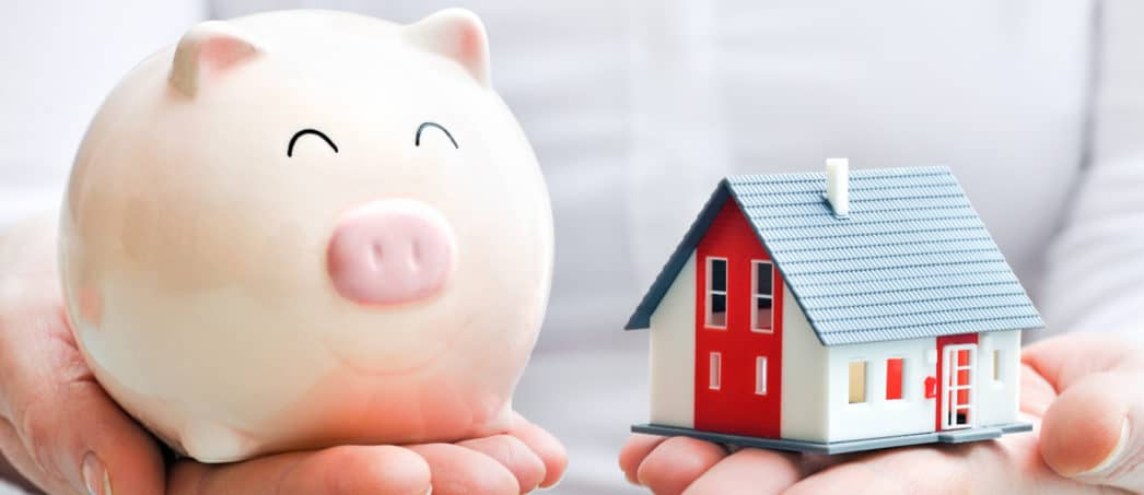 small piggy bank being held in one hand with a small house being held in the other hand; how are you going to pay for your new house